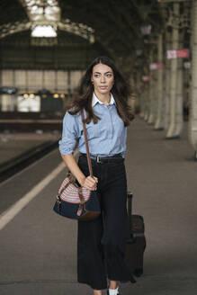 Young female traveller walking on train station - VPIF01727