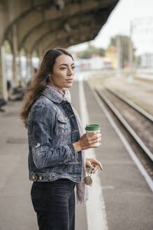 Young female traveller with coffee to go on train station - VPIF01739