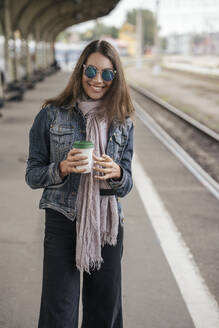 Young smiling traveller with coffee to go on train station - VPIF01742
