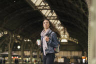 Young female traveller with coffee to go on the platform - VPIF01745