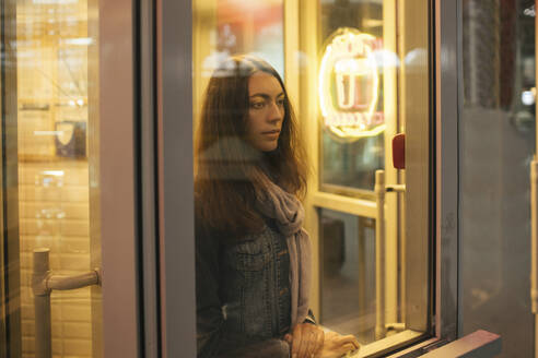 Young female traveller waiting and looking out of the window - VPIF01751