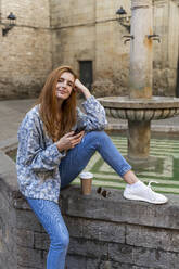 Woman using smartphone sitting on a fountain - AFVF04149