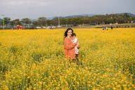 Portrait of happy woman with baby girl on her arms standing in a rape field, Gyeongju, South Korea - GEMF03238