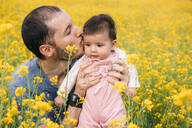 Portrait of baby girl kissed by her father in a rape field - GEMF03241