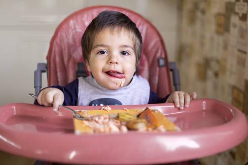 Portrait of little boy sitting on high chair eating vegetables - VGF00330