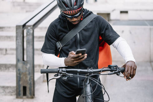 Stylish young man with bicycle, smartphone and messenger bag in the city - CJMF00156
