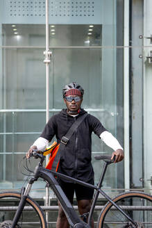 Portrait of stylish young man with bicycle and messenger bag in the city - CJMF00165
