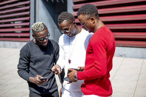 Three cool young men using cell phones in the city - CJMF00168