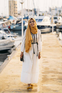 Young muslim woman wearing yellow hijab walking at the harbour - MPPF00215