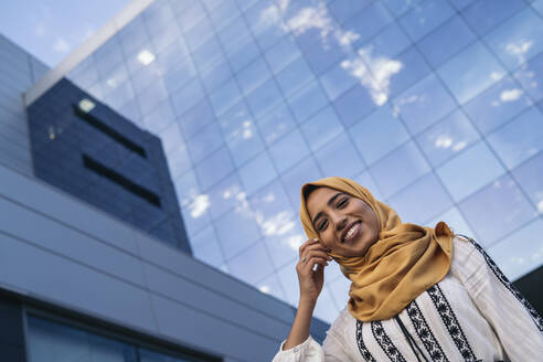 Young muslim woman wearing yellow hijab, building with glass facade in the background - MPPF00230