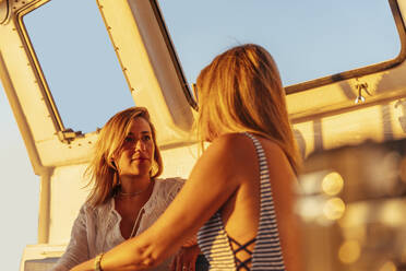 Friends talking during boat trip in the evening light - MOSF00110
