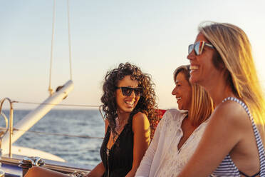 Friends laughing during boat trip in the evening light - MOSF00113