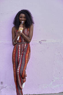 Portrait of young woman eating ice cream in front of purple wall - VEGF00782