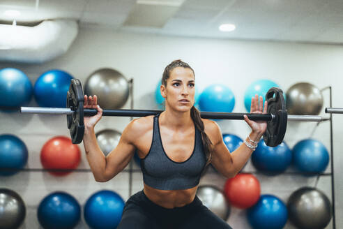 Woman exercising with weight in a gym - JCMF00255