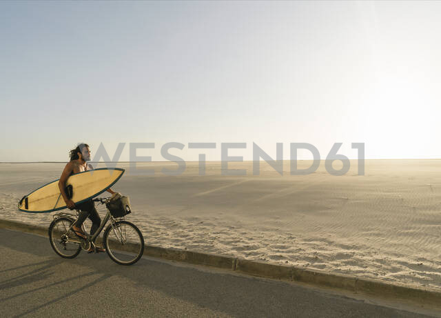 Surfer riding a bicycle during the sunset in the beach, Costa Nova, Portugal - AHSF01042 - Hernandez and Sorokina/Westend61
