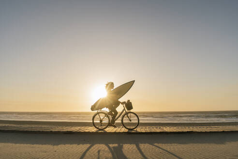 Surfer riding a bicycle during the sunset in the beach, Costa Nova, Portugal - AHSF01045
