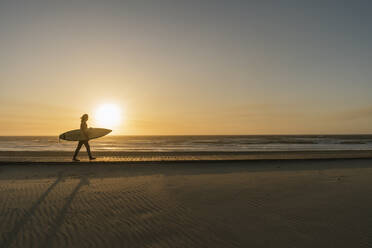 Surfer walking with the surfboard during the sunset at the beach - AHSF01048