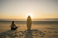 Rear view of a surfer doing meditation during the sunset at the beach - AHSF01051