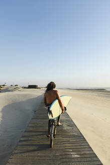 Surfer riding a bicycle during the sunset, holding surf board - AHSF01054