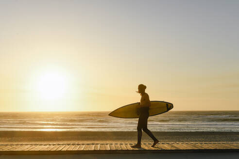 Surfer walking with the surfboard during the sunset at the beach - AHSF01057