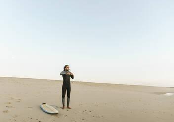 Portugal, Costa Nova, Surfer put on neoprene standing at the beach - AHSF01063