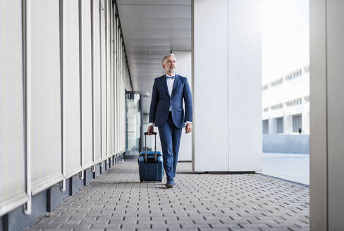 Mature businessman in a passageway with rolling suitcase on the go - DIGF08513