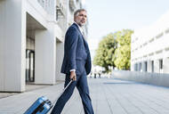 Mature businessman with rolling suitcase on the go in the city - DIGF08522