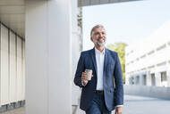 Smiling mature businessman with takeaway coffee on the go - DIGF08525