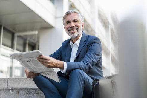 Smiling mature businessman sitting on stairs in the city with newspaper - DIGF08531
