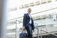 Mature businessman holding bag walking down stairs in the city - DIGF08540