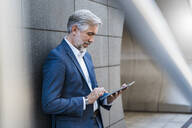 Mature businessman standing at a wall using tablet - DIGF08549