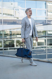 Fashionable mature businessman with travelling bag on the go - DIGF08555