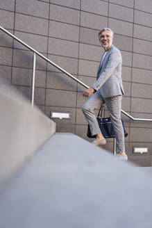 Fashionable mature businessman with bag walking up stairs - DIGF08570