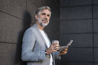 Fashionable mature businessman leaning at a wall with newspaper and takeaway coffee - DIGF08579