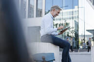 Smiling mature businessman using tablet in the city - DIGF08585