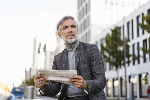 Fashionable mature businessman reading newspaper in the city - DIGF08618