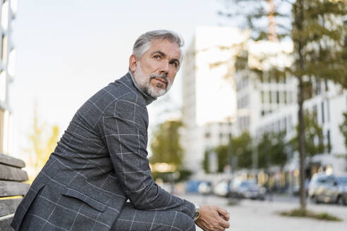 Portrait of fashionable mature businessman sitting on a bench in the city - DIGF08624