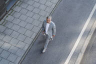 Top view of mature businessman walking on a road - DIGF08633