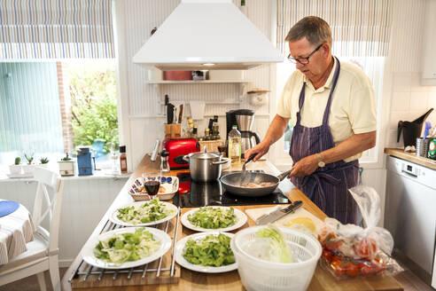 Senior man preparing meal in kitchen - JOHF04455