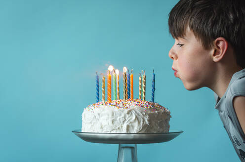 Boy blowing out candles on a birthday cake against blue background. - CAVF65890