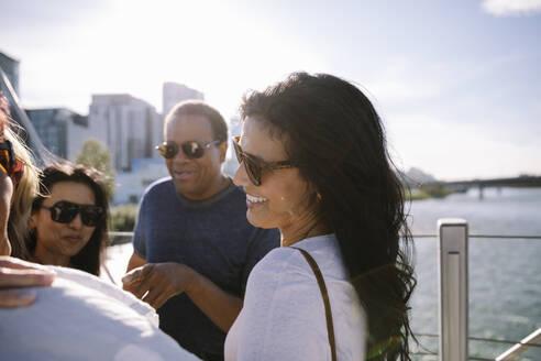 Happy woman talking with friends on sunny, urban bridge - HEROF39606