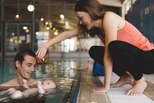 Parents with baby in swimming-pool - JOHF04546
