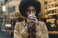 Young woman with afro hair having hot drink in front of cafe - CUF52566