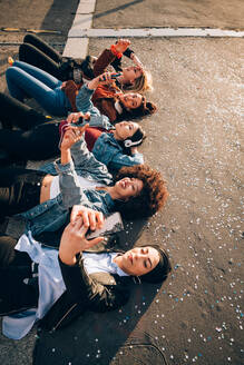 Friends together on kerb taking selfie and using smartphones, Milan, Italy - CUF52584