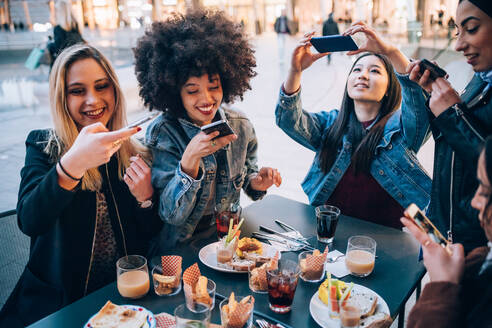 Friends taking photos of their food and drinks at outdoor cafe, Milan, Italy - CUF52707