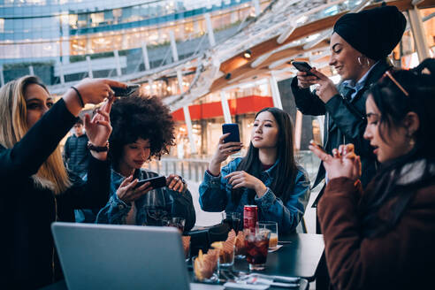 Friends taking photos of their food and drinks at outdoor cafe, Milan, Italy - CUF52758