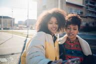 Two cool young female friends taking smartphone selfie on urban sidewalk - CUF52791