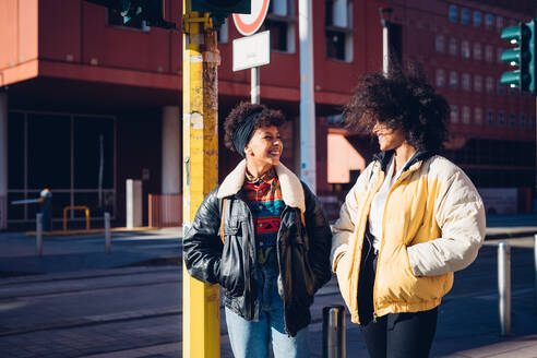 Two cool young female friends chatting in urban street - CUF52803
