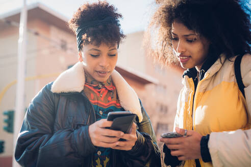 Two cool young women looking at smartphone on urban sidewalk - CUF52806