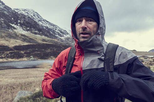 Male hiker with hood up in snow capped mountain landscape, portrait, Llanberis, Gwynedd, Wales - CUF52863